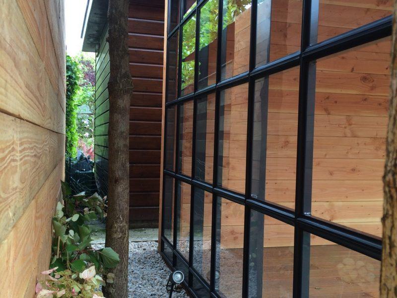 Een veranda voorzien van een aluminium/glazen wand met roede verdeling